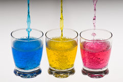 Three glasses with colored whater. Studio shot of coloured water pouring into three glasses Stock Photography