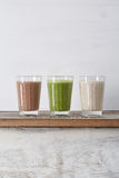 Three glasses of deep smoothies in the light background royalty free stock photography