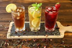 Three glasses of different cold tea drinks black, green with lemon and mint, hibiscus teas. Three glasses of different cold tea drinks black, green with lemon Stock Photos