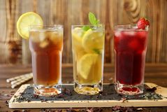 Three glasses of different cold tea drinks black, green with lemon and mint, hibiscus teas. Three glasses of different cold tea drinks black, green with lemon Royalty Free Stock Image