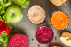 Three glasses of different fresh juice. Beet, carrot and apple juices on grey wood background royalty free stock photography