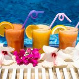Natural freshly squeezed juice by the pool with a straw. Three glasses of freshly squeezed orange, carrot and grapefruit juice by the pool Stock Photos