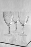 Three glasses. Three glass glass stand on the glass surface isolated on a grey background Royalty Free Stock Images