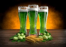 Three glasses of green beer with barley and hops. 3D render Stock Photography