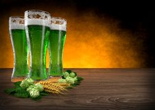 Three glasses of green beer with barley and hops. 3D render Royalty Free Stock Photography