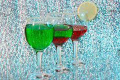 The three glasses of green and red liquor. The three glasses of transparent green and red liquor and lemon Royalty Free Stock Photography