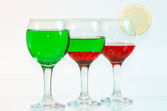 The three glasses of green and red liquor and lemo. The three glasses of transparent green and red liquor and lemon Stock Photography