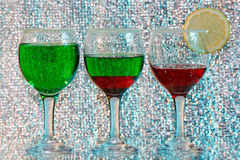 Three glasses of green and red liquor and lemon. The three glasses of transparent green and red liquor and lemon Stock Photography
