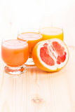 Three glasses of juice with cut in half grapefruit Royalty Free Stock Photo