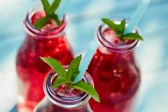 Three glasses of lemonade with raspberries Royalty Free Stock Photos