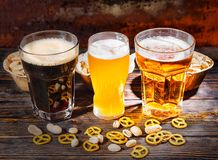 Three glasses with light, unfiltered and dark beer near plates w Royalty Free Stock Photography