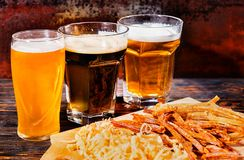 Three glasses with light, unfiltered and dark beer stand near wo Royalty Free Stock Photo