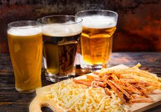 Three glasses with light, unfiltered and dark beer stand in a ro stock photography