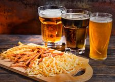 Three glasses with light, unfiltered and dark beer stand in a row near wooden cutting board with snacks on dark desk stock images