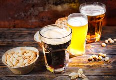 Three glasses with light, unfiltered and dark beer stand in a ro Stock Photos