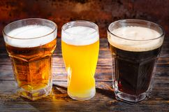 Three glasses with light, unfiltered and dark beer on wooden des Royalty Free Stock Image
