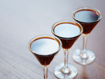 Three glasses of liquor on wooden table closeup Royalty Free Stock Photography