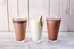 Three glasses of milkshakes. Three glasses of sweet milkshakes on the white surface stock photo