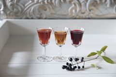 Three glasses with multicolored liqueur on a white vintage background stock images
