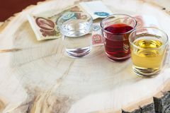 Three glasses and old money of the USSR on the tree stump, stylistics under the wild nature of uncouthness royalty free stock photos