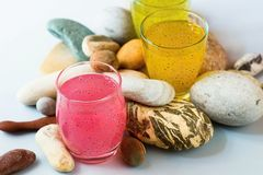 Three glasses with pastel color fruit drinks lies between pile of various decorative pebbles. Stock Photo