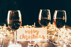 Red wine and merry christmas card. Three glasses with red wine on wooden table with fairylights, candles and merry christmas card Stock Photography