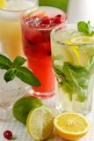 Three glasses of refreshing drink Mohito. Classic mint, cranberry and orange on a table with slices of lemon, lime and a bowl of ice Royalty Free Stock Image