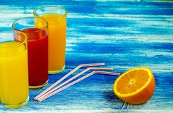Three glasses of soft drinks are on a blue background. Slices of an orange. Summer drinks and healthy lifestyle. royalty free stock images