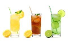 Three glasses of summer lemonade, iced tea, and limeade drinks isolated on white stock images