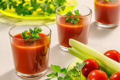 Three glasses of tomato juice decorated with parsley or coriander leaves. Next is a plate of parsley, tomatoes and celery stems stock image