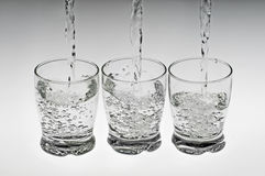 Three glasses with water. Studio shot of three glasses with water on a white surface Stock Image