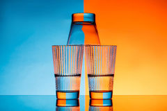Three glasses with water over blue and orange background. Royalty Free Stock Images