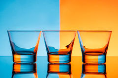 Three glasses with water over blue and orange background. Stock Images