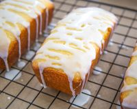 Glazed Lemon Cake on Black Cooling Rack. Three glazed lemon cakes on a black cooking rack with brown parchment paper Stock Photos