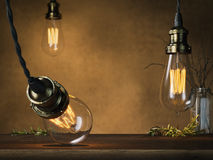 Three glowing vintage bulbs and empty table. 3d rendering Stock Images