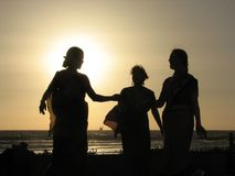 The three Goddesses. Three women dancing on sunset stock photography