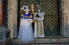 Three going to Carnivale. Three costumed people going to mardi gras carnivale in Venice Italy and standing in Saint Marks square royalty free stock image