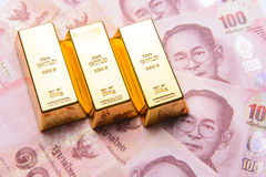 Three gold bar with thai hundred baht bills Stock Image