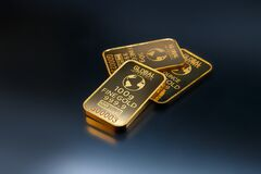 Three Gold Bars Against Dark Background Stock Photography