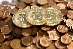 Three gold bitcoins are on a pile of other coins stock photography