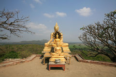 Three gold buddha statues located near the cliff Stock Image
