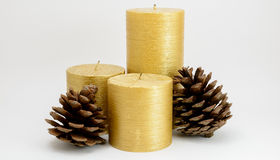 Three Gold Candles with Pine cones Stock Photos