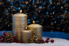 Three Gold Candles in snow Stock Photos