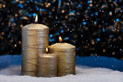 Three Gold Candles in snow Stock Photo