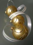 Three gold christmas balls. And white ribbon Stock Photo