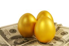 Three gold eggs. To a heap with money Stock Photos