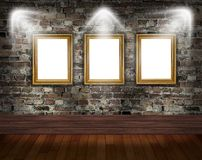 Three gold frames on brick wall Stock Photography