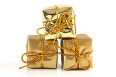 Three gold gift rapped parcels. Gold gift rapped parcel pyramid on white background royalty free stock photography