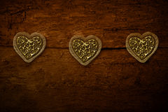Three gold hearts on old wooden background Royalty Free Stock Photo