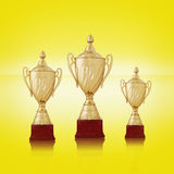 Three gold trophies on bright yellow background Stock Photos
